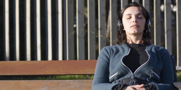 Woman listening to music through headphones
